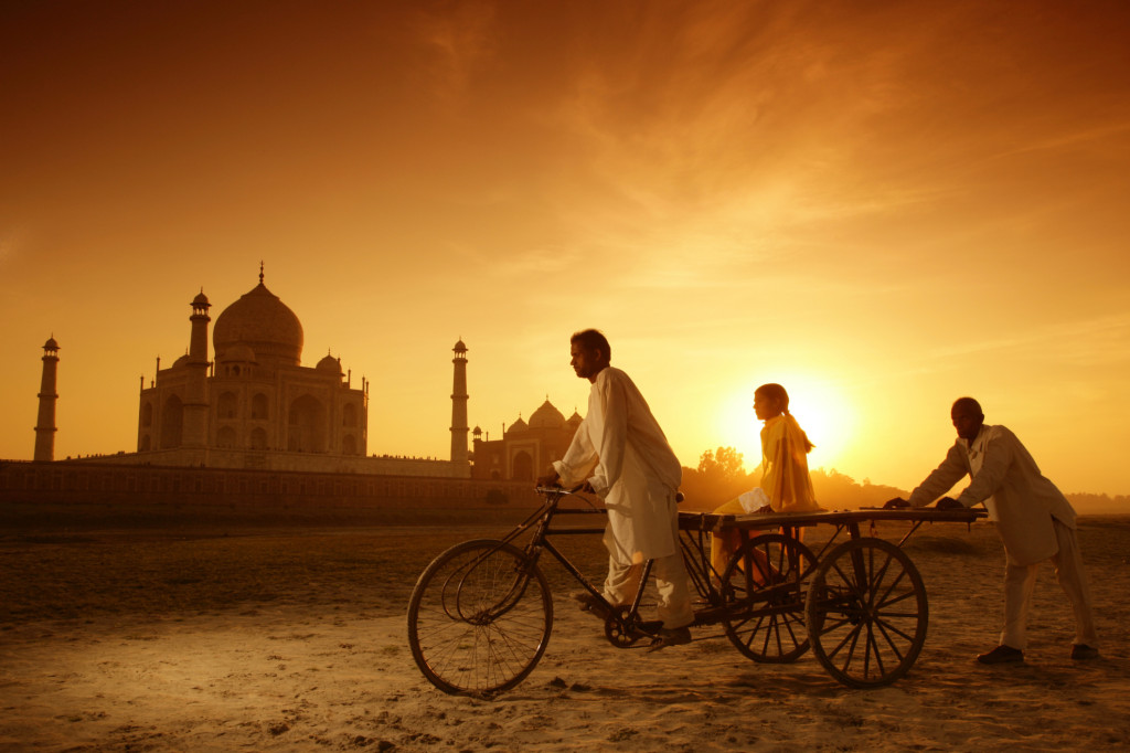 India, Uttar Pradesh, Agra Man on bike with girl on trailer and man pushing from behind in front of Taj Mahal at sunset