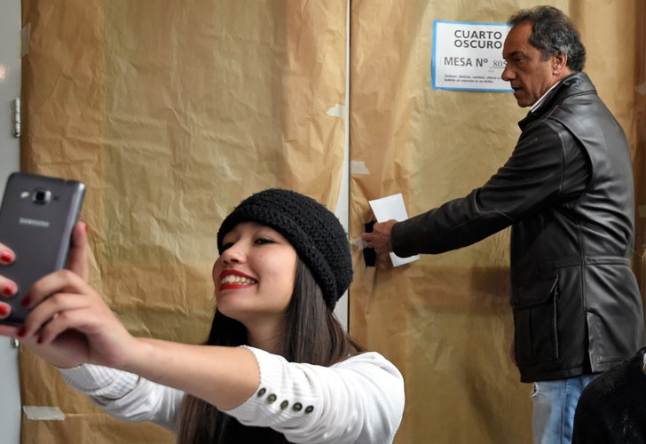 A voter takes a delighted selfie with the kirchnerista candidate Daniel Scioli in the background. (AFP)