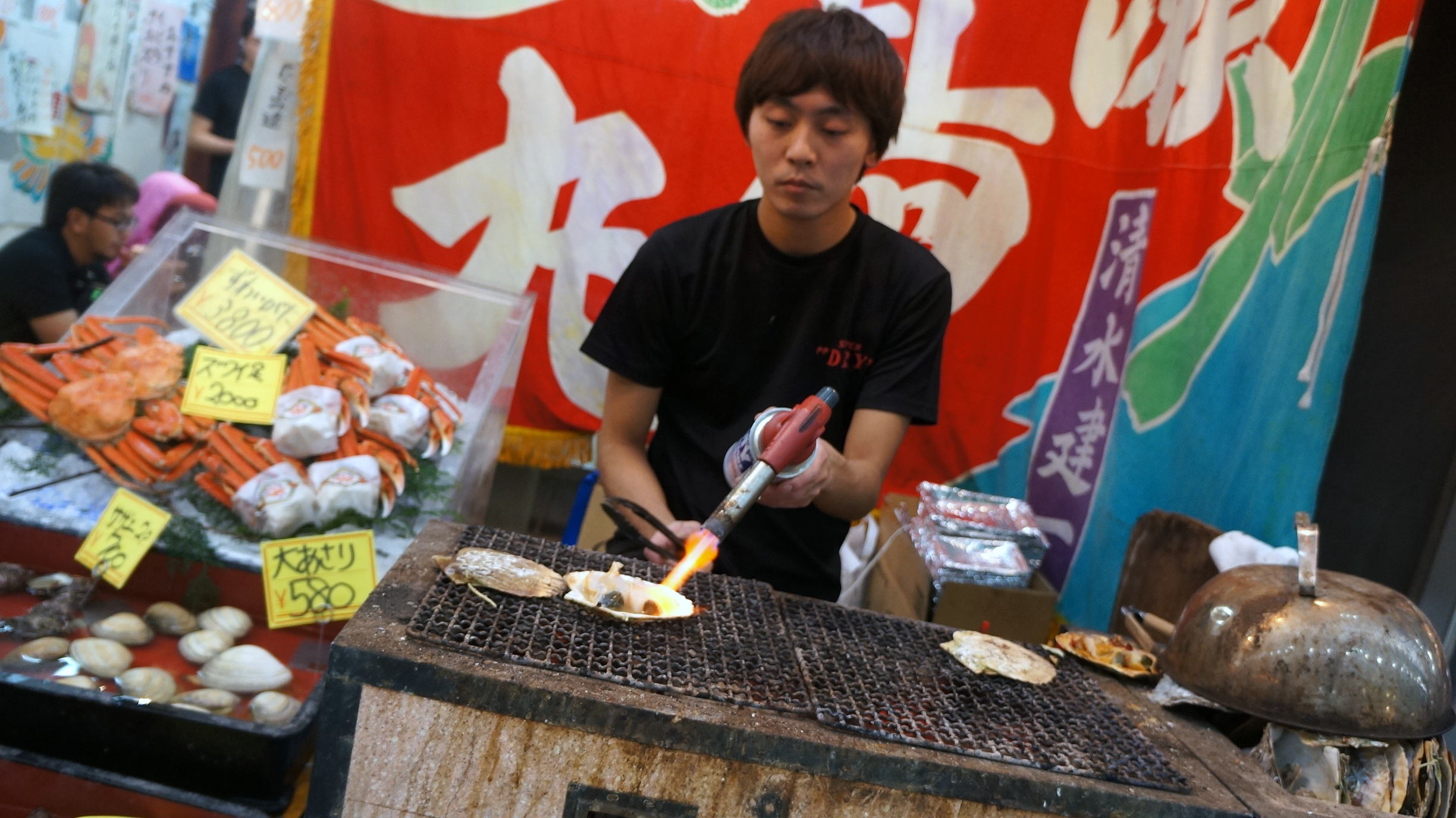 Taking a blowtorch to a fresh scallop in Kuromon market in Osaka.